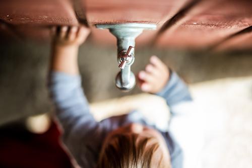 Jungen und Technik - Faszination Kind Kleinkind Garten Wasserhahn Wassertropfen beobachten niedlich wasserknappheit Dürre betrachten zu Wand Holzwand erkunden