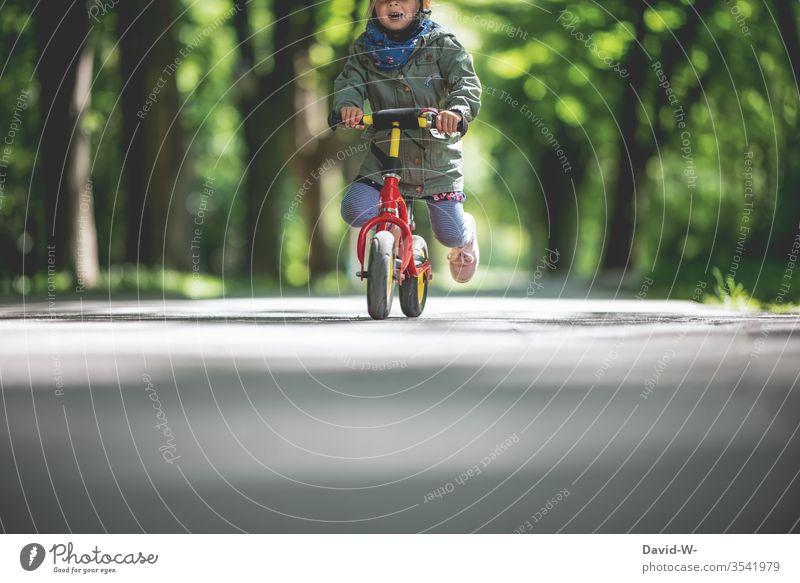 Kind fährt mit dem Fahrrad draußen durch die Natur Kindheit Freude Fahrradfahren klein Kleinkind Mädchen niedlich schnell Kinder Lächeln Mund Lenker festhalten