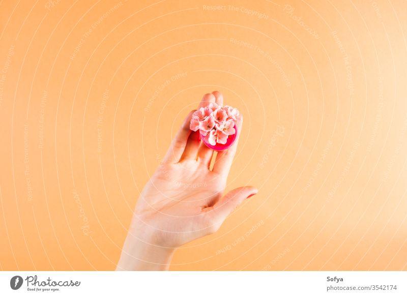 Rosa Menstruationstasse in der weiblichen Handfläche keine Verschwendung Blumen rosa wiederverwendbar alternativ menstruell Minimalismus modern orange organisch