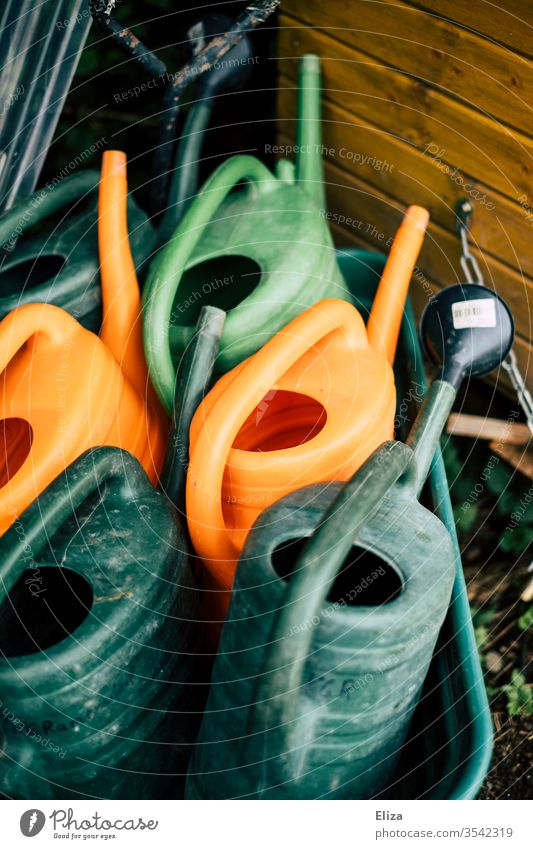 Verschiedenfarbige Gießkannen bunt grün orange Gartenarbeit Gärtner Wasser Geräte gießen leer Tag