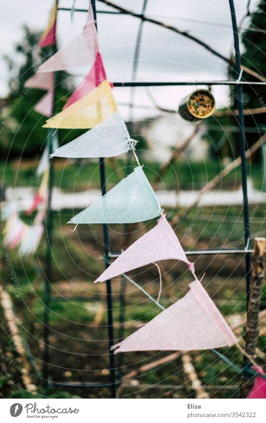 Eine bunte Wimpelkette als Dekoration im Garten bewölkt grau aufhübschen dekorieren Tristesse Dekoration & Verzierung Feste & Feiern Partydekoration Gartenparty