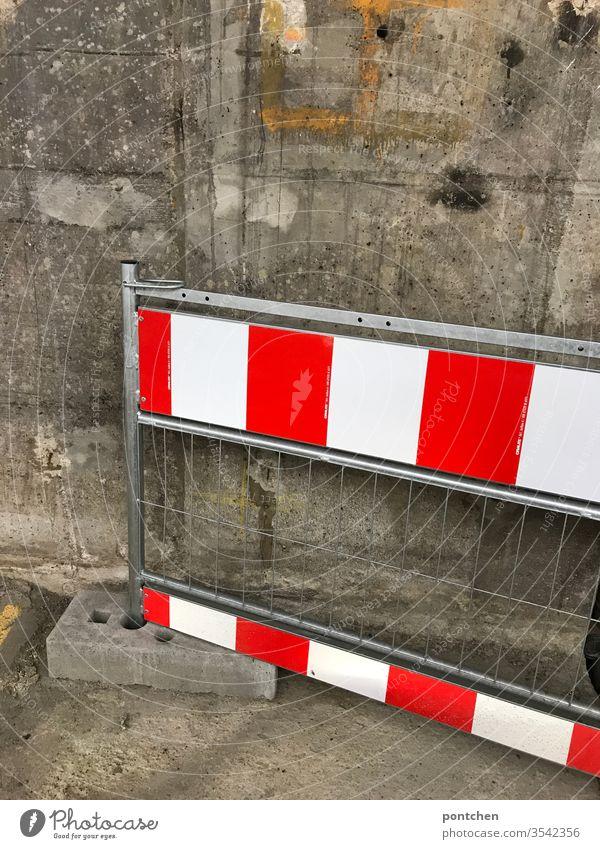 Eine  Absperrschranke rot-weiß gestreift lehnt an einer Betonwand Absperrung absperrschranke warnung verbot streifen gitter Dreckig Außenaufnahme Farbfoto