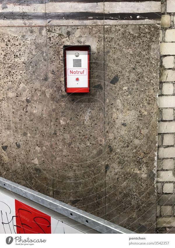 Notruf Anlage mit rotem knopf angebracht  an einer  Hausfassade. Gefahr, Sicherheit, Bedrohung . alarm vorrichtung Wand Schranke gestreift rot-weiß Absperrung