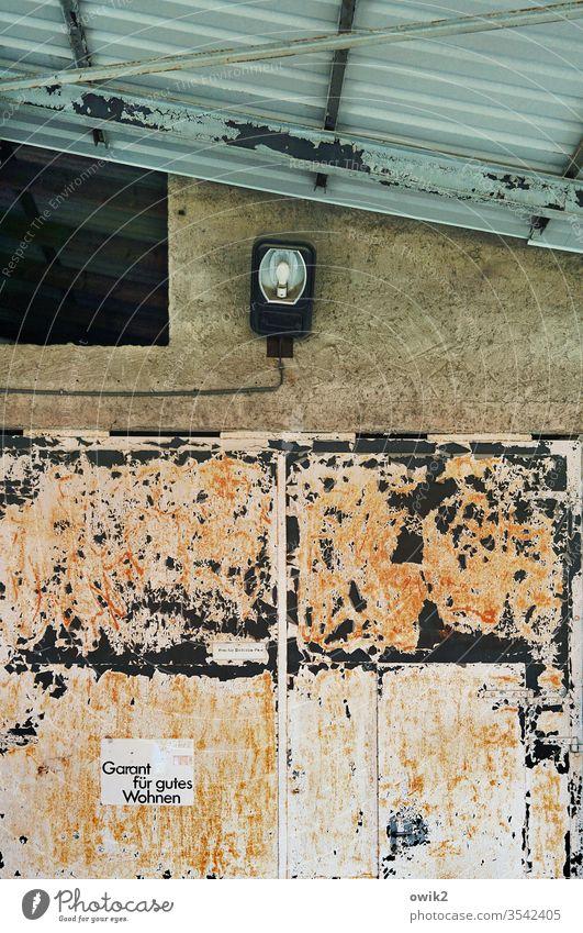 Werbekonzept Garage Tor Blech Metall Rost alt Vergänglichkeit trashig Wand Ecke Lampe Detailaufnahme Dach Blechdach Dachschräge Spuren Verfall abblättern Farbe