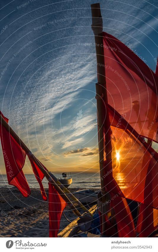 Die Flaggen der Fischerboote vor dem Sonnenlicht baabe Ostsee Strand schön Schönheit Boot Cloud Wolken Küstenlinie Handwerk früh Fischen Netzstrümpfe Fahne