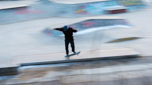 Ein Eiskunstläufer in Bewegung bei einem Stunt Aktion aktiv Aktivität Kunst fantastisch Gleichgewicht Berlin Unschärfe-Effekt verschwommen Holzplatte Großstadt