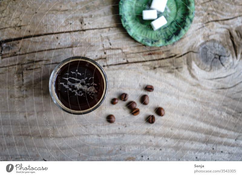 Kaffee in einem Glas und Würfelzucker auf einem grünen Teller. Rustikaler Holztisch, Draufsicht. Getränk Espresso glastasse stark aromatisch Koffein Früstück