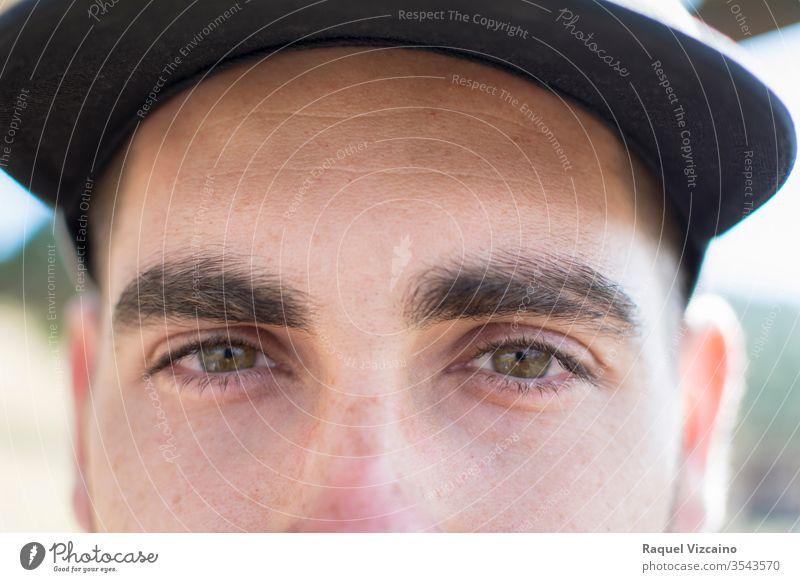 Nahaufnahme der grünen Augen eines kaukasischen Jungen mit einer Mütze. Porträt Aussehen teuer Regenbogenhaut Pupille Registerkarten Vordergrund abschließen