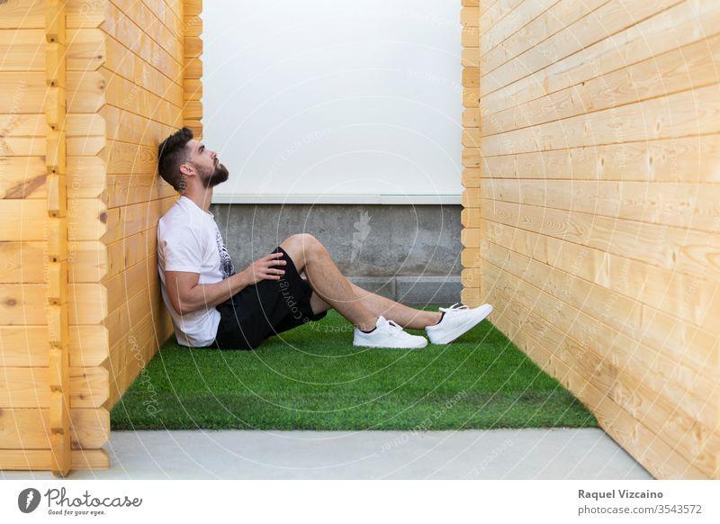 Ein hübscher Mann sitzt auf dem Kunstrasen zwischen zwei Holzhütten. gutaussehend sitzend Gras Kabine weiß Gesundheit Erholung Wellness Haus heimwärts Zen