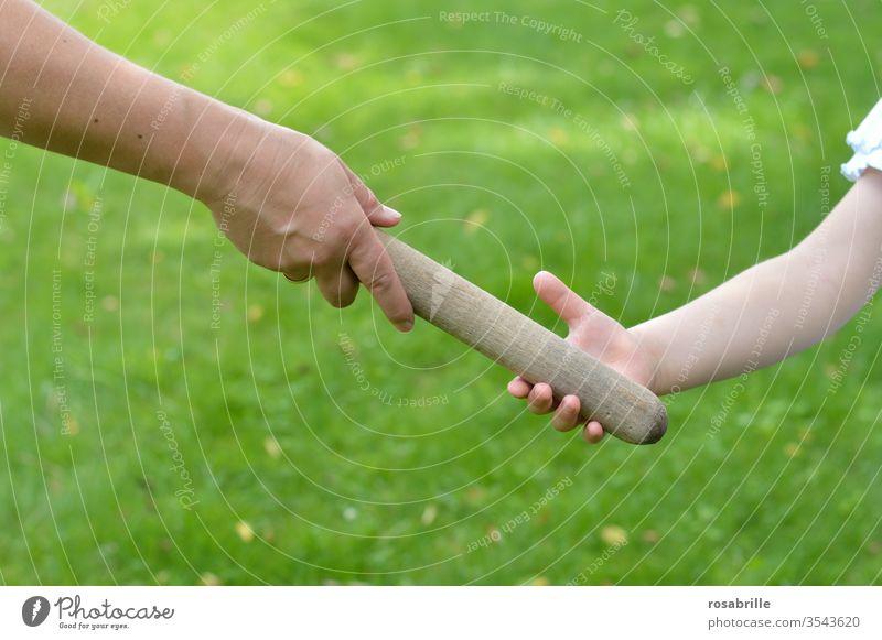 wörtlich genommen | das Staffelholz an die nächste Generation abgeben – Hand einer Mutter gibt den Staffelstab an ihr Kind, die Tochter weiter bei einem Wettlauf im Freien