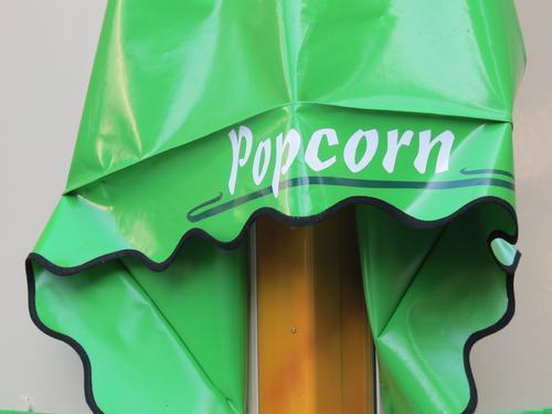 Werbung für Popcorn auf grüner Lackfolie Schriftzeichen Buchstaben Wort Typographie Schilder & Markierungen Hinweisschild Außenaufnahme Farbfoto weiß Mitteilung