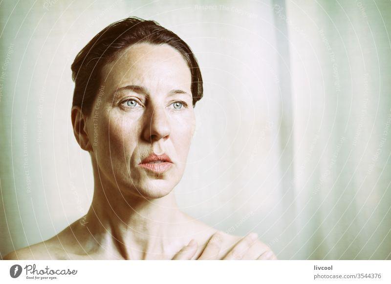 eine erwachsene Frau, die in ihre Tagträume eingetaucht ist reif lieblich Erwachsener Senior Schatten Licht Posen Porträt Denken weiblich Lifestyle