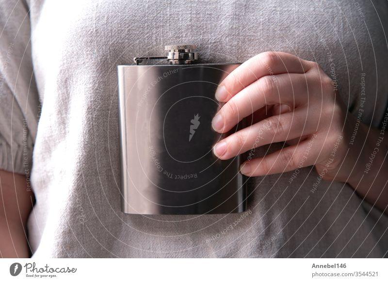 Hand hält einen Flachmann aus Edelstahl für Likör-, Alkohol- und Getränkekonzepte in Nahaufnahme Hintergrund alkoholisch trinken Design Schnaps Party Stahl