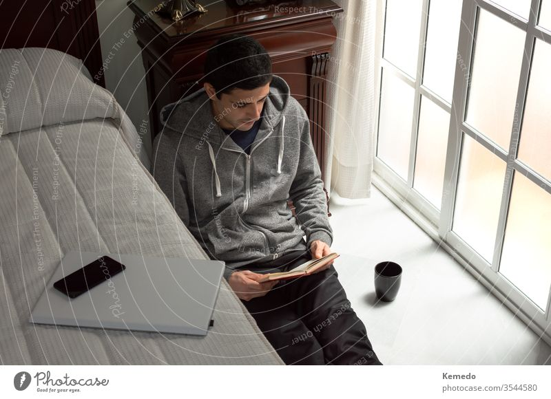 Junger Mann verlässt die Technik, um zu Hause ein Buch zu lesen. Konzept der digitalen Entgiftung, Zeit zu Hause verbringen. Entzug Technik & Technologie