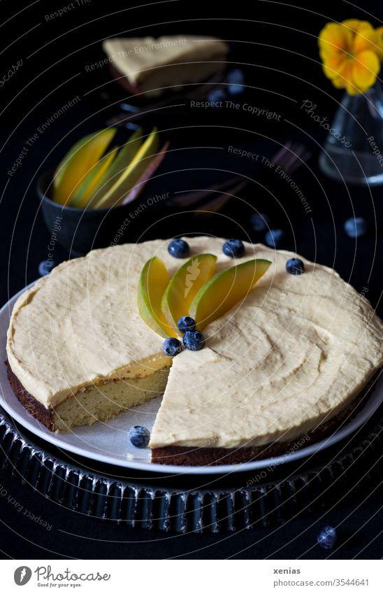 Süßer, runder Kuchen mit weißer Schokolade und Mangocreme, dekoriert mit Blaubeeren und Mangospalten, Kuchenstück und Vase im dunklen Hintergrund Backform