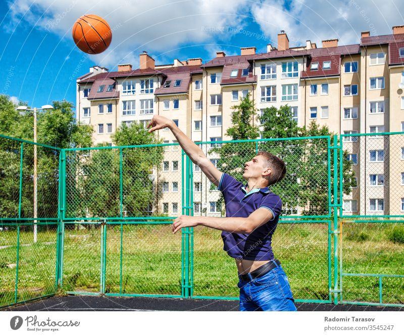 junger Mann trainiert an einem sonnigen Sommertag auf dem Spielplatz bei einem Basketballspiel Training Ball Sport aktiv Athlet Spieler passen Gericht Lifestyle