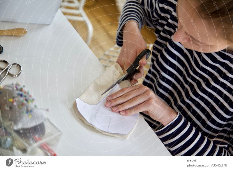 Tapferes Schneiderlein | Junge Frau schneidet mithilfe eines Schnittmusters ein Stück Stoff an ihrem Nähtisch zu. Nähen Schneidern Handarbeit nähzubehör Schere