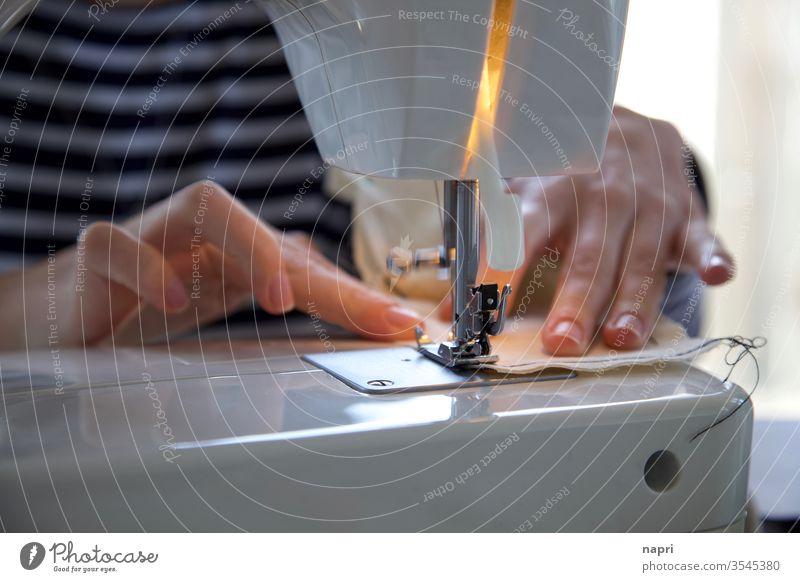 Hände einer jungen Frau schieben ein Stück Stoff durch den Fuß einer Nähmaschine. Nähen Schneidern Handarbeit Naht Faden Handwerk Kreativität Freizeit & Hobby