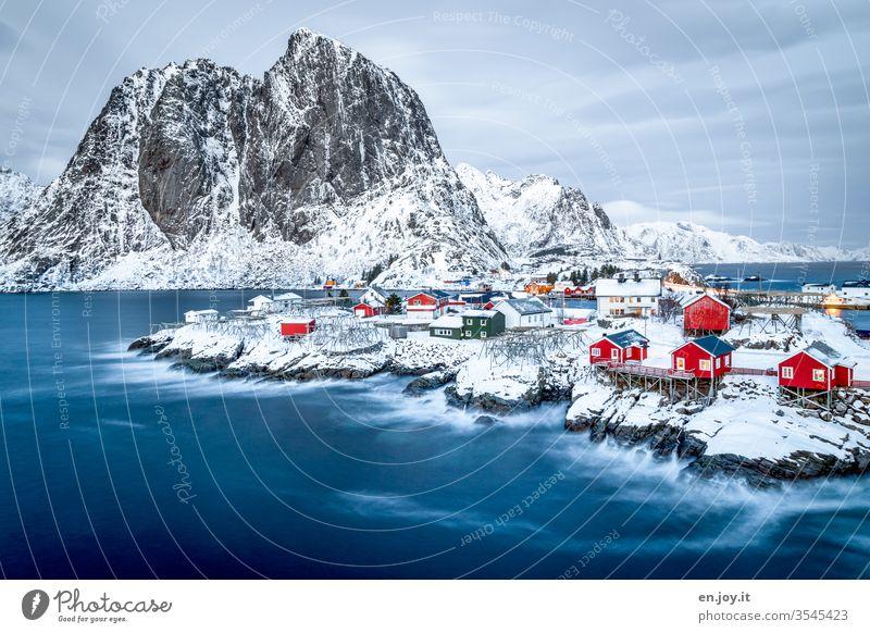 Hamnoy auf den Lofoten mit Aussicht auf die kleinen roten Häuschen die auf verschneiten Felsen stehen zur blauen Stunde Norwegen Skandinavien Hamnøy Rorbuer