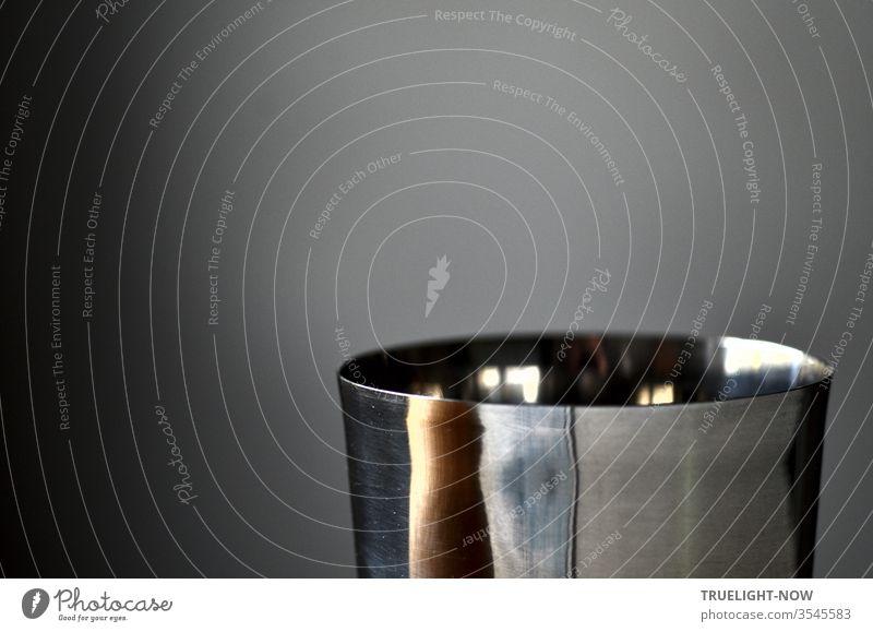 Der obere Teil eines polierten Edelstahl Bechers spiegelt vor grauem Hintergrund Tageslicht Reflexe und in verzerrter Form Teile seiner Umgebung: Versuch zur buddhistischen Herz-Sutra