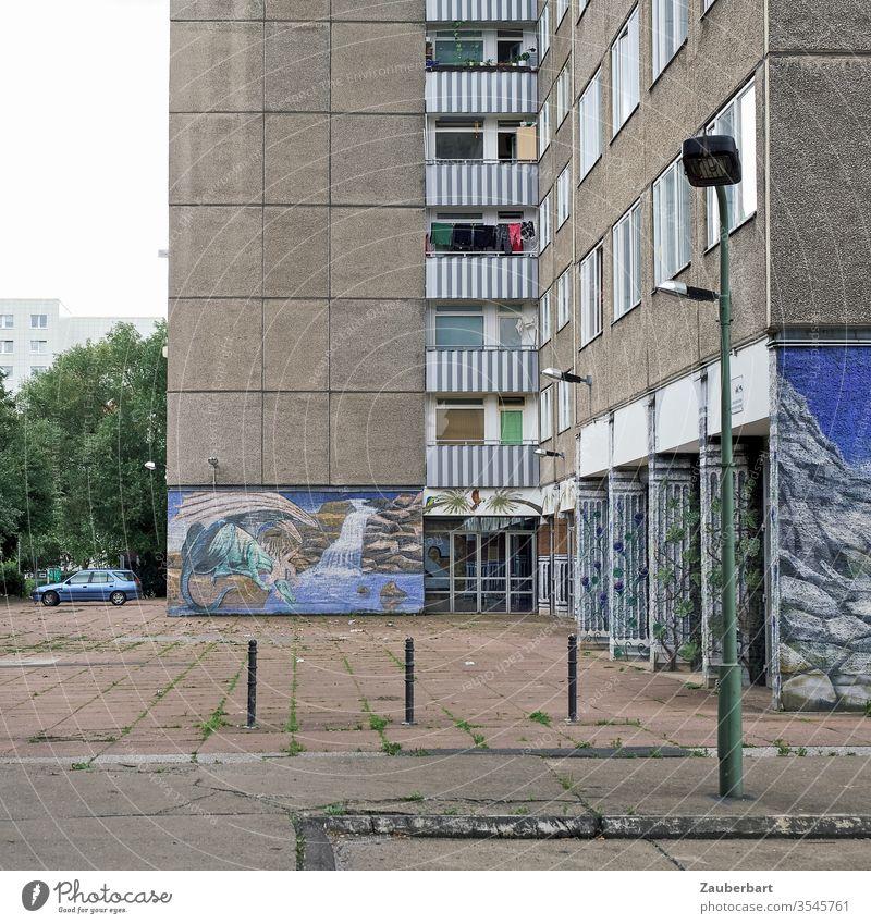 Plattenbau mit Hof, Gehweg, Malereien und Laterne Fassade Wohnhaus Berlin Lichtenberg blau Wandmalerei Poller Gebäude Stadt Menschenleer Haus Fenster Balkon