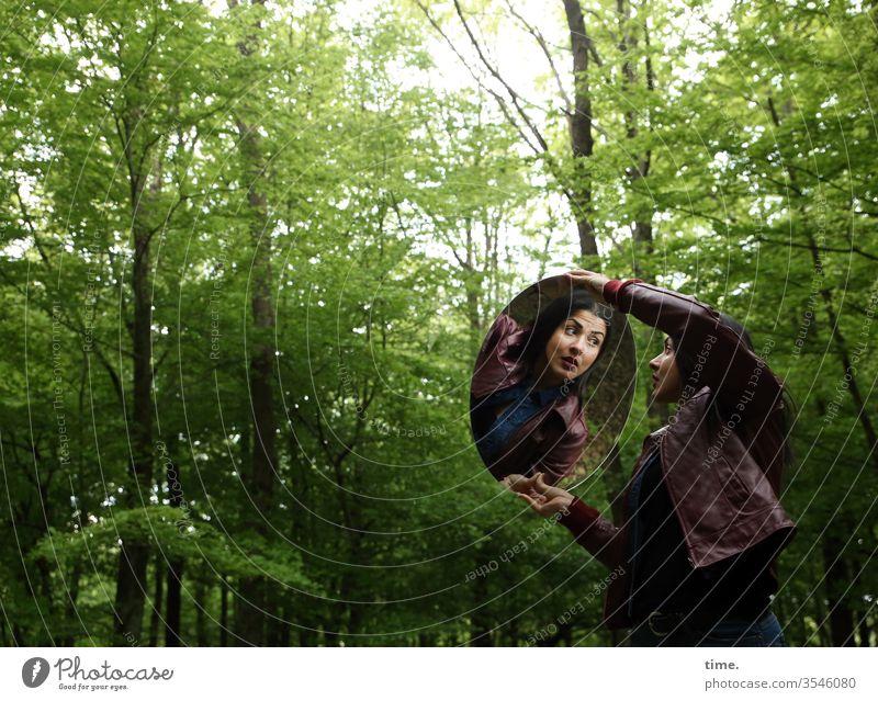 Estila frau feminin wald schauen beobachten dunkel grün wild langhaarig dunkelhaarig lederjacke spiegel halten erstaunt laubwald