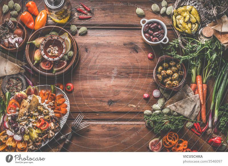 Gesunde vegane oder vegetarische Ernährung mit Snacks. Verschiedene frische, eingelegte und fermentierte Gemüse in Schalen. Hummusteller mit geröstetem Gemüse und Nüssen. Oliven, Feigen, grüne Mandeln, Kichererbsen