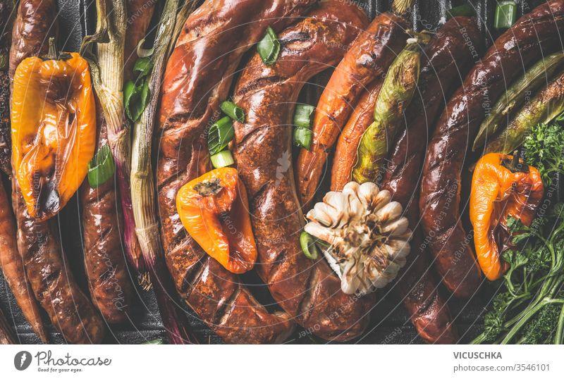 Nahaufnahme von schmackhaften Grillwürsten und gebratenem Gemüse. Ansicht von oben. Grillparty-Platte abschließen geschmackvoll gegrillt Würstchen Draufsicht