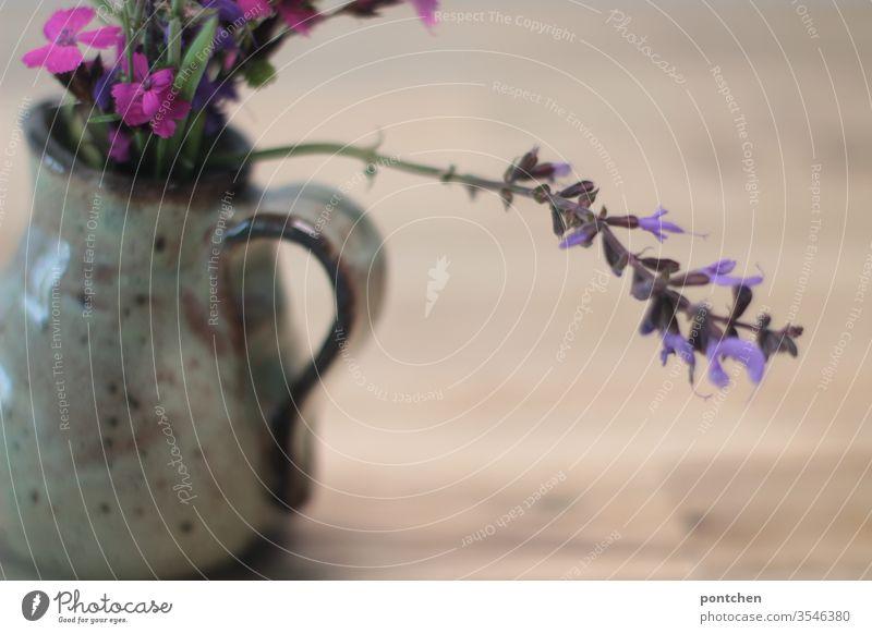 Kartäuser Nelke, Eisenkraut Salbei. Blumenstrauß aus wiildblumen in einer Vase aus Ton auf einem Holztisch Blühend Frühling Blüte dekoration gelb lila bunt pink