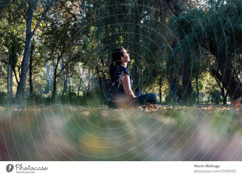 Schöne Frau sitzt auf Gras vor der Sonne und macht Yoga Rücken Gleichgewicht Konzentration Übung passen Fitness Lotos meditieren meditierend Meditation mental