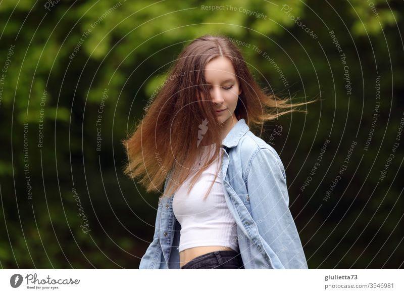 Porträt einer hübschen fröhlichen jungen Frau, Teenager mit langen Haaren, im Park Halbprofil Wegsehen Bewegungsunschärfe Schatten Licht Tag Außenaufnahme