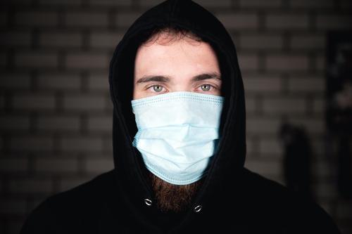 Porträt eines jungen Mannes mit medizinischer Schutzmaske für das Covid-19-Coronavirus-Konzept. Schützen Sie Ihre Gesundheit. Hintergrund covid-19 Business