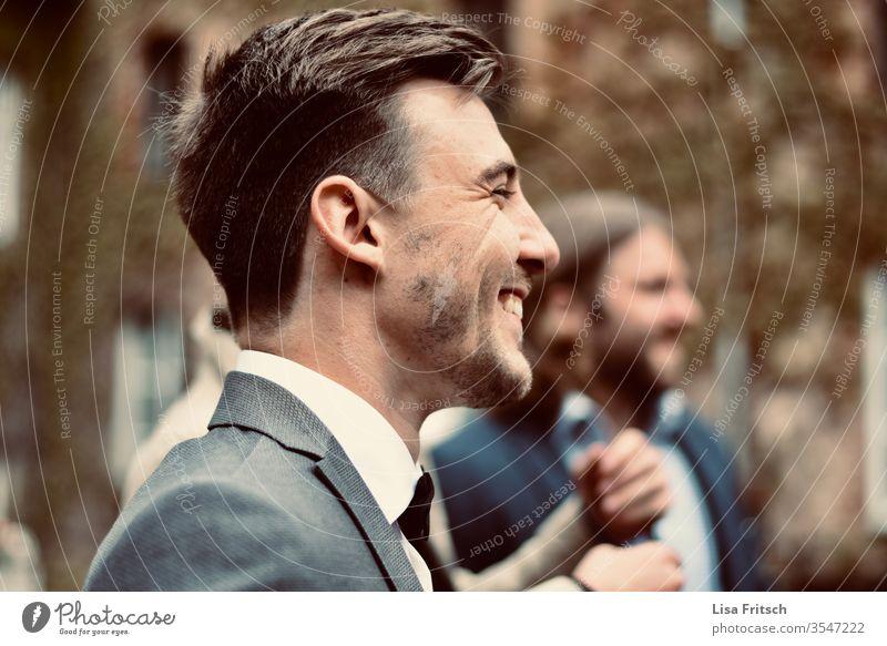 Mann - glücklich - lachen - genießen 18-30 Jahre brünett Anzug Anzugträger Bart Lachfalte hübsch Freude Gast Hochzeit Spaß haben gemeinsam grau Junger Mann