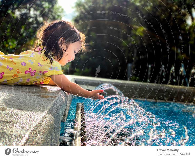 Mädchen spielt mit Wasserfontäne bei Sonnenschein Lifestyle Erfrischung Geplätscher Sonnenlicht Kleinkind wenig Person Licht Lachen erwärmen Sprinkleranlage