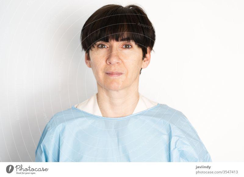 Arzt mittleren Alters zieht Schutzkittel an Frau Krankenpfleger medizinisch Krankenhaus Gerät Virus Korona Labor schützend covid-19 Medizin Hintergrund Mädchen