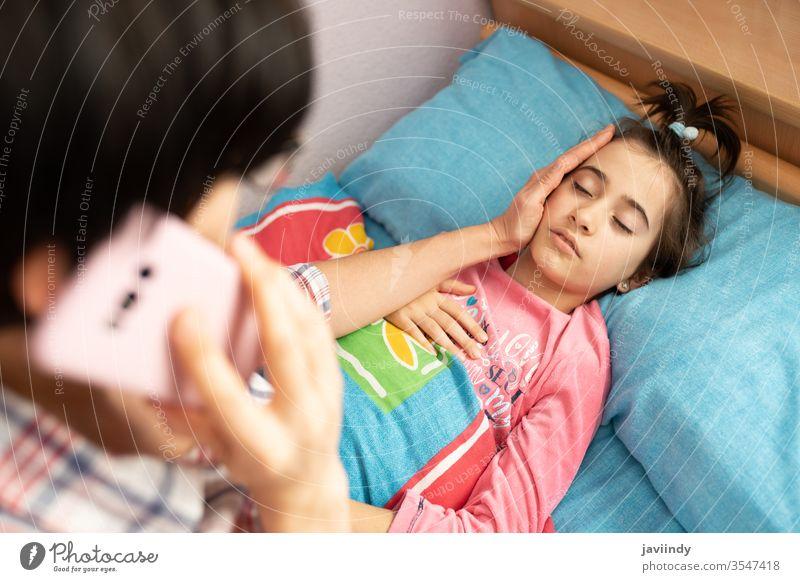 Mutter besorgt über die Temperatur ihrer Tochter und ruft den Arzt Thermometer Mädchen Fieber Kaukasier Menschen Pflege Krankheit Grippe kalt krank unwohl Anruf
