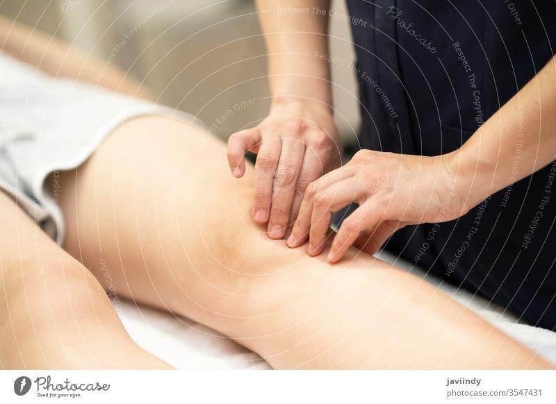Physiotherapeutin, die eine Behandlung am Knie einer Frau durchführt. Physiotherapie Bein Chiropraktiker Therapie physisch geduldig Reha Klinik Pflege