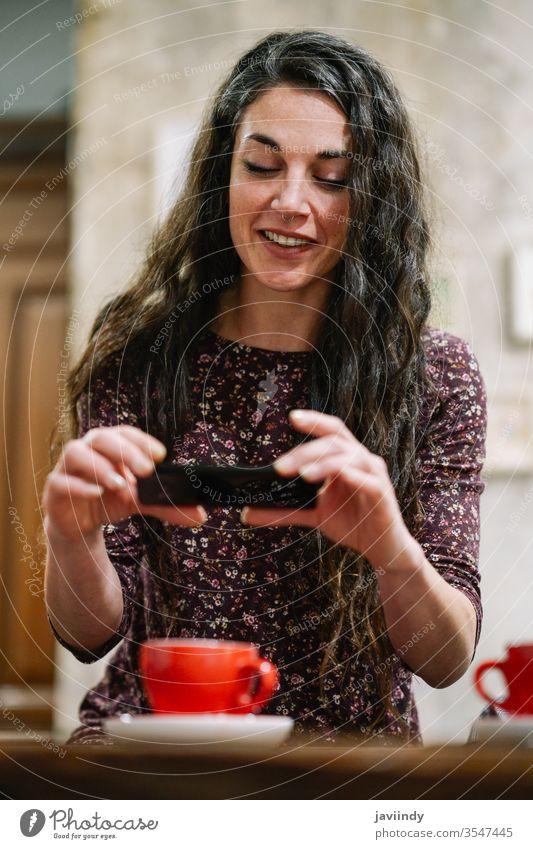 Junge Frau mit einigen grauen Haaren, die ein Smartphone in einem Cafe benutzt. Café Kaffee graues Haar Kaukasier weiß Foto Person Tasse Mädchen Erwachsener