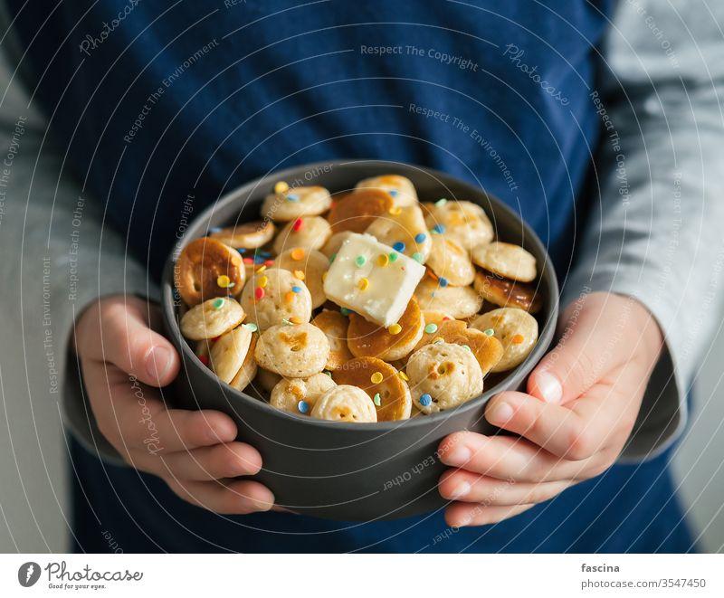 Pfannkuchenmüsli in Babyhänden, Kopierfeld Pfannkuchen-Getreide winzige Pfannkuchen Mini-Pfannkuchen Kind Müsli Hände Textfreiraum Halt Nahaufnahme Streusel