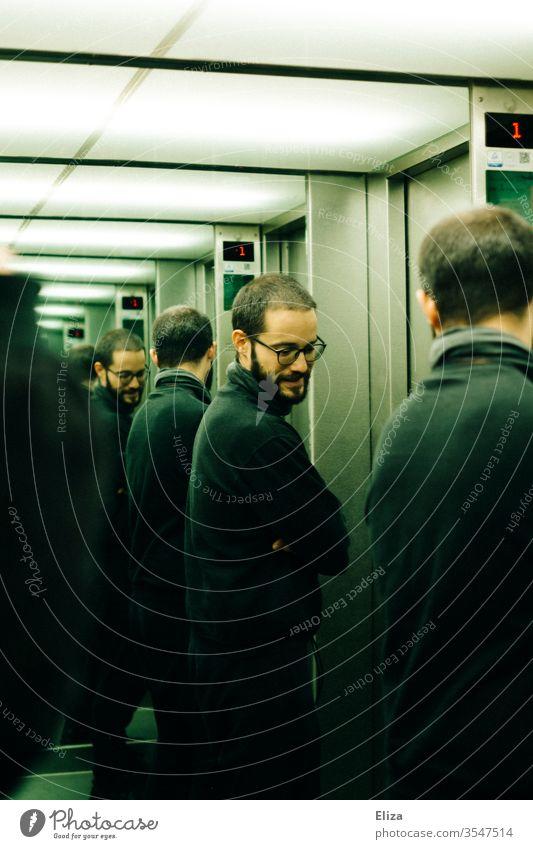 Ein Mann, der sich mehrmals in den Spiegeln eines Fahrstuhls spiegelt Brille Spiegelung Persönlichkeiten Multiple Persönlichkeit unendlich ernst