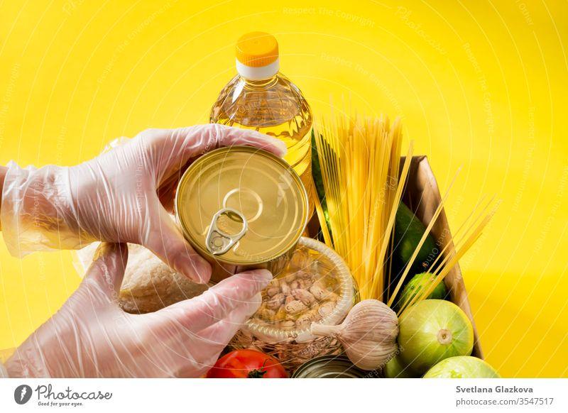 Spende. Lebensmittelversorgungskrise Lebensmittelvorrat für die Quarantäne-Isolationsperiode auf gelbem Hintergrund. Reis, Erbsen, Getreide, Konserven, Öl, Gemüse, Maske, Desinfektionsmittel. Nahrungsmittellieferung, Coronavirus.