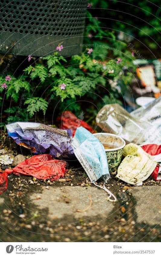 Medizinischer Mundschutz der neben anderem Müll auf dem Boden liegt Maske MNS Dreck weggeworfen dreckig eklig unbrauchbar Mülltonne verbraucht benutzt