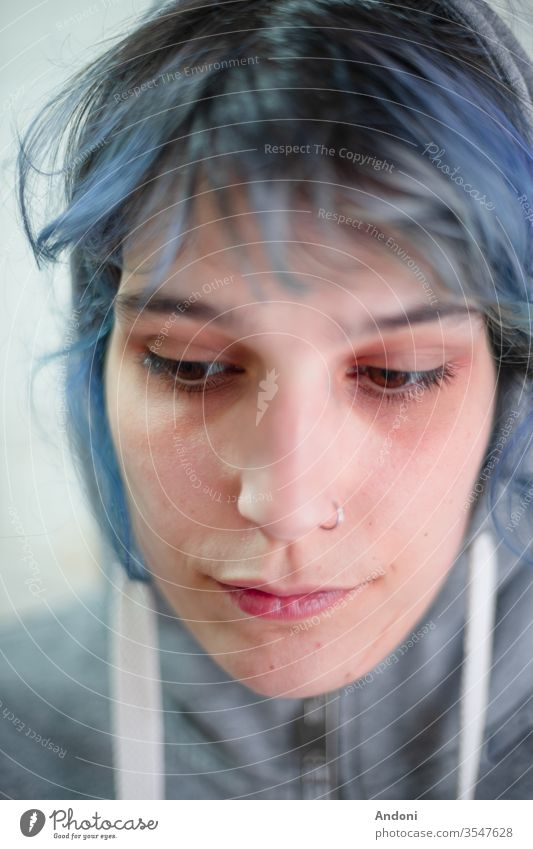 Mädchen mit Piercing und Kapuze sieht niedergeschlagen aus blau Wind Erwachsene Textfreiraum links Farbfoto kleines Mädchen lange Haare Einsamkeit