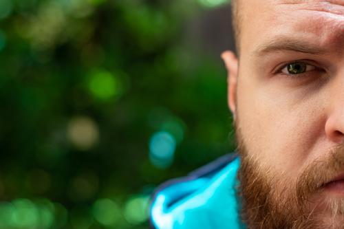 Halber Kopf eines kahlköpfigen, bärtigen Mannes sichtbar, grünes, ernsthaft trauriges Auge leuchtet im Fokus auf grünem Waldhintergrund. Erwachsener wütend