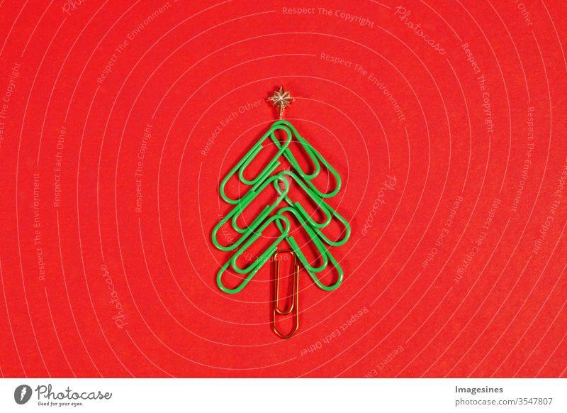 Frohe Weihnachten im Büro. Weihnachtsbaum aus Büroklammern auf dem roten Hintergrund. Büroklammer Weihnachtsbaum. Weihnachtshintergrund. Textfreiraum rechts