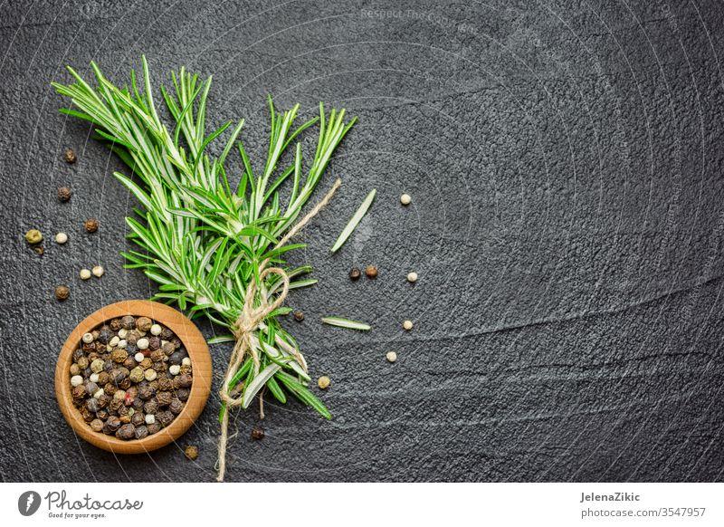 Gewürze und Kräuter über schwarzem Steintisch Rosmarin Bestandteil frisch Kraut roh organisch Essen zubereiten Lebensmittel grün Küche Pflanze Natur Gesundheit