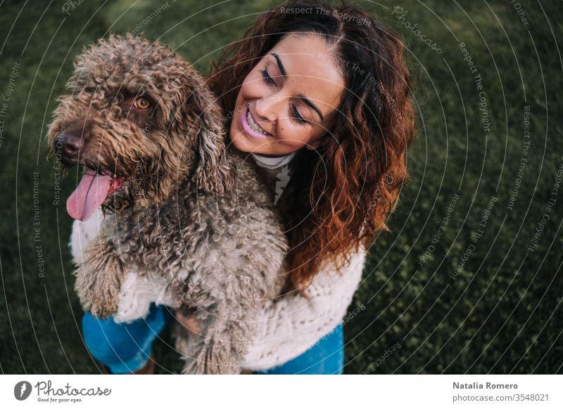 Eine schöne Frau ist mit ihrem Hund auf der Wiese. Die Besitzerin umarmt ihr Haustier, während sie es mit Liebe anschaut. Sie genießen einen Tag im Park. Das Haustier ist ein spanischer Wasserhund mit braunem Fell.