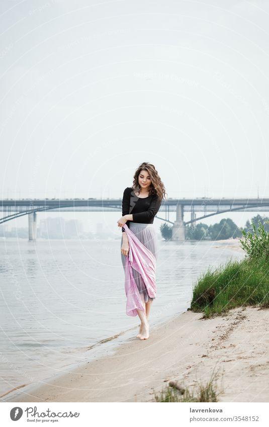 Junge Frau, die mit einem rosa Schal in der Hand am Strand spazieren geht, selektiver Fokus Erwachsener Rücken Schönheit Braut Kaukasier Kleid gesichtslos