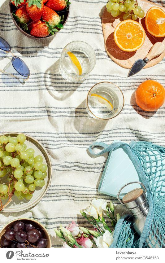 Femininer Sommerpicknick-Flachleger, Früchte, Beeren und Zitronenwasser auf gestreifter Baumwolldecke Brille Wasser Zitrusfrüchte saisonbedingt frisch Trauben