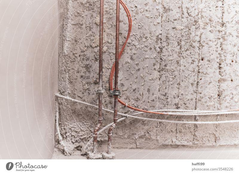Wasserleitung, Rohrleitung und Kabel  im Rohbau Putzfassade Montage Wand Baustelle Fassade Mauer graue Wand Metall Stahlkabel Leitung Wasserrohr verbinden